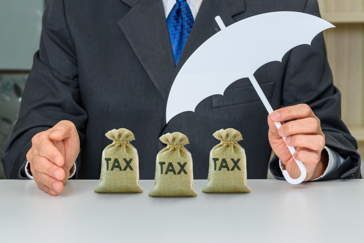 Taxpayer uses a hand and umbrella to protect tax bags